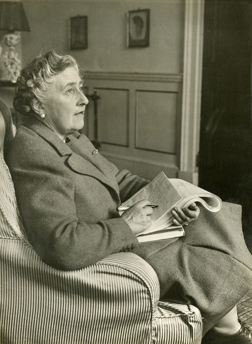 Agatha Christie sitting with newspaper making notes
